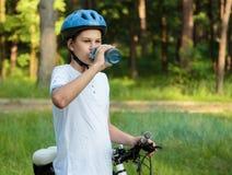 O menino novo no capacete e no ciclista branco da camisa de t bebe a água da garrafa no parque Menino bonito de sorriso na bicicl foto de stock