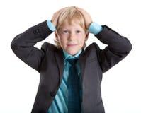 O menino novo no terno abraçou sua cabeça, olhando a câmera, fundo branco isolado Fotografia de Stock Royalty Free