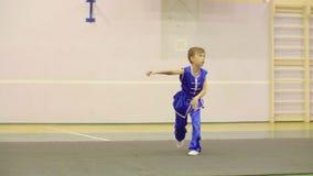O menino novo no vestido chinês nacional está praticando o formulário de Nanquan do qui do wushu TAI de Kung Fu video estoque