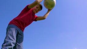 O menino novo pinga a bola contra o céu azul, movimento lento