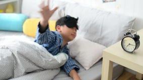 O menino novo que dorme e desliga quedas do despertador fora da cama video estoque
