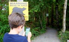 O menino novo que joga Pokemon vai não ver o perigo Fotografia de Stock Royalty Free
