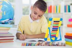 O menino novo que senta-se em sua mesa em casa e aprende Imagens de Stock Royalty Free