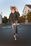 O menino novo salta com o 'trotinette' na rua Fotografia de Stock Royalty Free