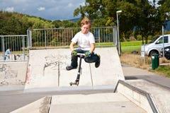 O menino novo salta com 'trotinette' sobre uma rampa na SK Imagens de Stock Royalty Free