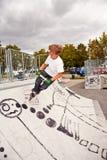 O menino novo salta com 'trotinette' sobre uma rampa na SK Imagem de Stock Royalty Free