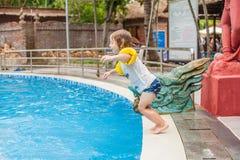 O menino novo salta na água da piscina Foto de Stock