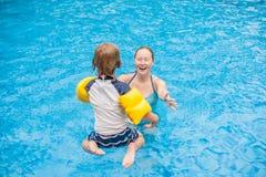 O menino novo salta na água da piscina foto de stock royalty free