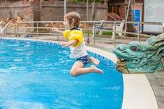 O menino novo salta na água da piscina Imagens de Stock