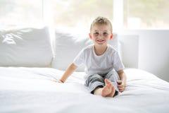 O menino novo senta-se na cama em casa foto de stock