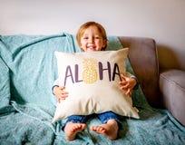 O menino novo senta-se no sofá imagens de stock royalty free