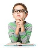 O menino novo sonhar acordado quando livro de leitura fotos de stock royalty free