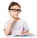 O menino novo sonhar acordado quando livro de leitura fotografia de stock royalty free