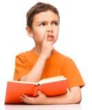 O menino novo sonhar acordado quando livro de leitura imagem de stock