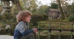 O menino novo toma uma respiração profunda ao sentar-se na extremidade de uma ponte ao lado de uma lagoa em um jardim japonês vídeos de arquivo