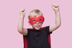 O menino novo vestiu-se no traje do super-herói com os braços aumentados sobre o fundo cor-de-rosa Imagem de Stock Royalty Free