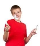 O menino, o adolescente a primeira vez tenta ter um shave e é confuso Foto de Stock