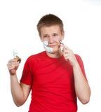 O menino, o adolescente a primeira vez tenta ter um shave e é confuso Imagens de Stock