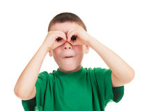 O menino olha através das mãos como binóculos Foto de Stock