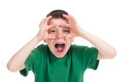 O menino olha através das mãos como binóculos Imagem de Stock Royalty Free