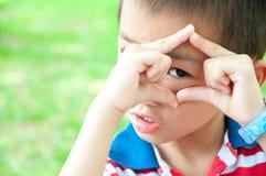 O menino olha através de uma estrutura das mãos imagens de stock royalty free