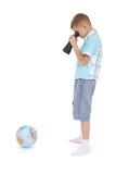 O menino olha através do campo-vidro no globo Imagens de Stock