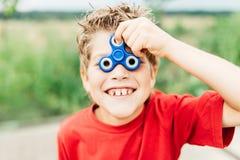 O menino olha através do spiner Imagens de Stock