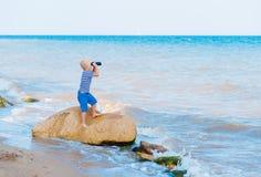 O menino olha através dos binóculos Fotos de Stock Royalty Free