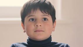 O menino olha a câmera com entusiasmo e surpresa vídeos de arquivo