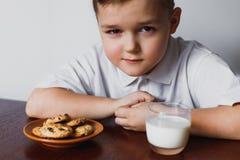 O menino olha com suspeita Biscoitos e leite Foto de Stock Royalty Free
