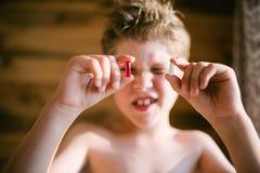 O menino olha desagradavelmente no comprimido Fotografia de Stock Royalty Free