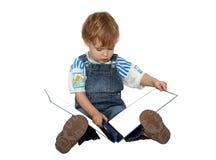 O menino olha em white pages no álbum azul Fotografia de Stock Royalty Free