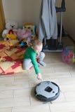 O menino olha o robô o aspirador de p30 Fotos de Stock Royalty Free