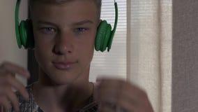 O menino põe fones de ouvido nas orelhas filme