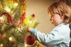 O menino pendura o brinquedo do Natal fotografia de stock