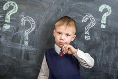 O menino pensa os pontos de interrogação imagens de stock