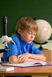 O menino pequeno é concentrado com leitura imagens de stock royalty free