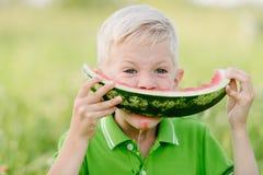 O menino pequeno bonito da criança com cabelos louros que come a melancia summergarden dentro imagens de stock