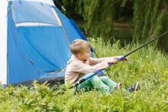 O menino pequeno bonito senta-se perto de uma barraca com uma vara de pesca em suas mãos Imagem de Stock Royalty Free