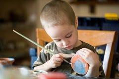 O menino pequeno causa dor ao frasco da argila Fotografia de Stock Royalty Free
