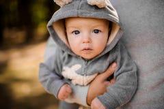 O menino pequeno com os olhos cinzentos pensativos olha atentamente de assento nas mãos dos pais Fotos de Stock