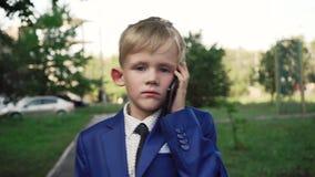 O menino pequeno com uma cara séria em um terno de negócio está andando abaixo da rua e está falando no telefone video estoque