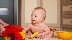 O menino pequeno da criança joga no construtor, sentando-se em casa no assoalho video estoque