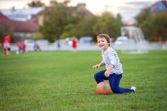 O menino pequeno da criança que joga o futebol e o futebol, tendo o divertimento excede Imagens de Stock Royalty Free