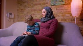 O menino pequeno divertido que joga o jogo na tabuleta e sua mãe muçulmana no hijab observa sua atividade em casa filme
