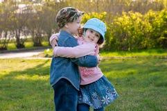 O menino pequeno e a menina andam e abraçam no parque imagem de stock