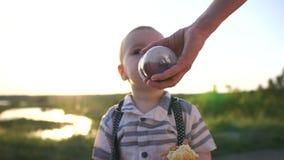 O menino pequeno está bebendo de uma garrafa de bebê que a mamã sustente no por do sol no movimento lento vídeos de arquivo