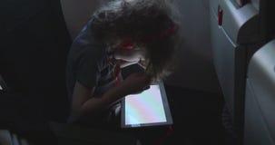 O menino pequeno joga jogos em seu tablet pc em um avião filme