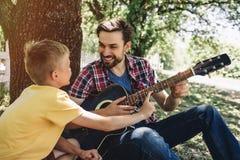 O menino pequeno leeaning para genar a guitarra do ` s Quer jogar nele O indivíduo farpado está guardando esta guitarra e está so imagem de stock