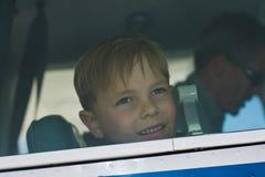 O menino pequeno olha para fora o indicador do avião Fotografia de Stock Royalty Free